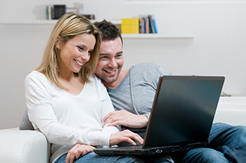 Couple sitting on a couch smiling while looking at a laptop computer