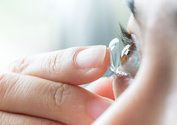 Woman putting in contact lenses