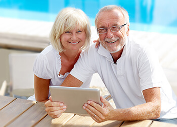 Older Woman and Man Reading a Tablet